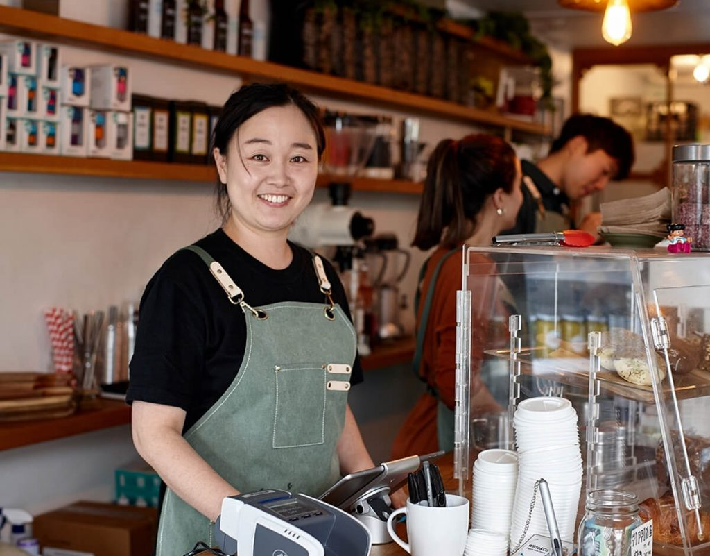 Young woman working at a cafe ready to take your order