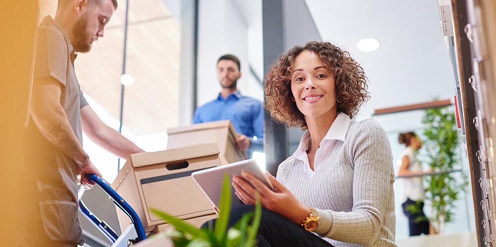 Woman smiling into camera as her business relocation is happening around her